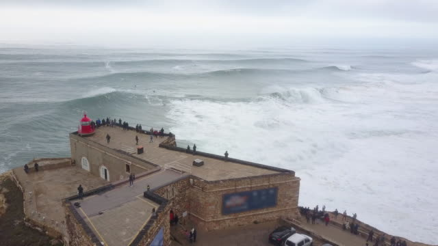 vídeos de stock e filmes b-roll de aerial drone view of surfers surfing huge waves and the lighthouse at nazare, portugal. - time-lapse - rebentação