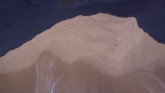 Aerial drone view of the beach ocean coastline waves sea and cliffs.