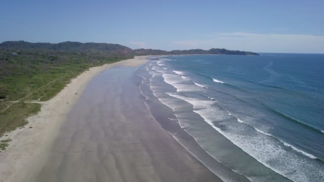 Aerial drone view of the beach, rocks and tide pools in Guiones, Nosara, Costa Rica.
