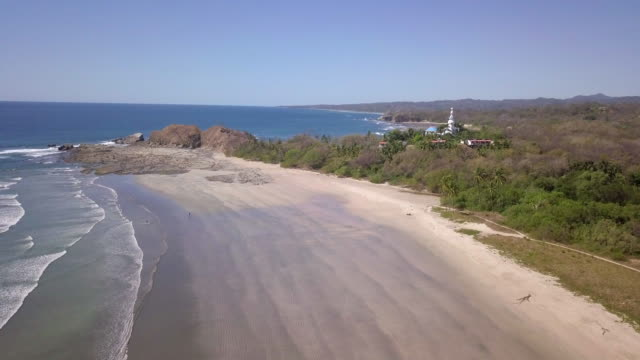 aerial drone view of the beach, rocks and tide pools in guiones, nosara, costa rica. - goodsportvideo stock videos and b-roll footage