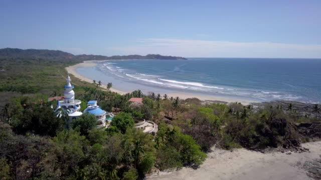 aerial drone view of the beach, rocks and tide pools in guiones, nosara, costa rica. - nosara stock videos and b-roll footage