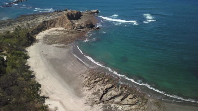 aerial drone view of the beach, rocks and tide pools in playa palada, guiones, nosara, costa rica. - goodsportvideo stock videos and b-roll footage
