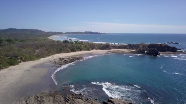 aerial drone view of the beach, rocks and tide pools in playa palada, guiones, nosara, costa rica. - nosara stock videos and b-roll footage