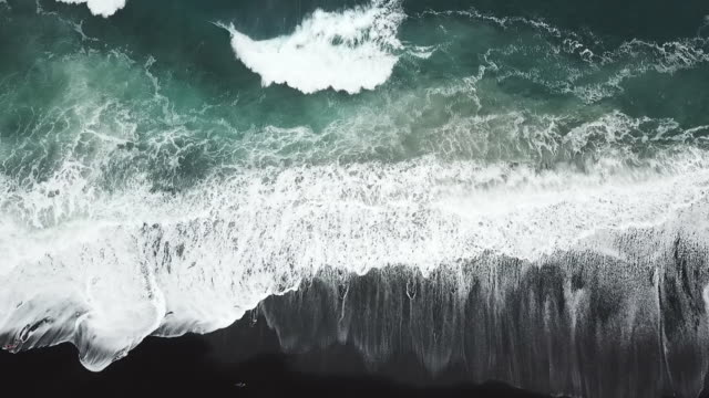 aerial drone view of the beach with black sand and the sea with waves - black sand stock videos & royalty-free footage