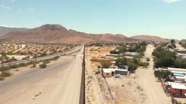aerial drone view of the border wall dividing sunland park, new mexico and port anapra, mexico - surrounding wall stock videos & royalty-free footage