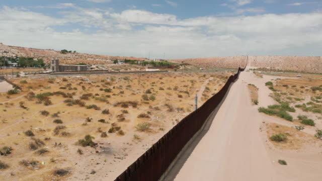 vidéos et rushes de vue aérienne de drone du mur frontalier divisant le parc de sunland, nouveau-mexique et port anapra, mexique - mur