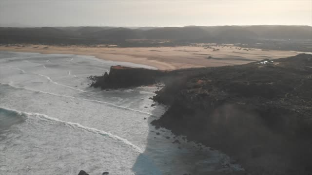aerial drone view of the deserted empty rocky beach and cliffs in portugal. - algarve stock-videos und b-roll-filmmaterial
