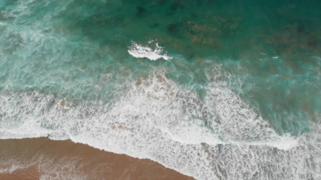 aerial drone view of the deserted empty rocky beach and cliffs in portugal. - spiritualität stock-videos und b-roll-filmmaterial