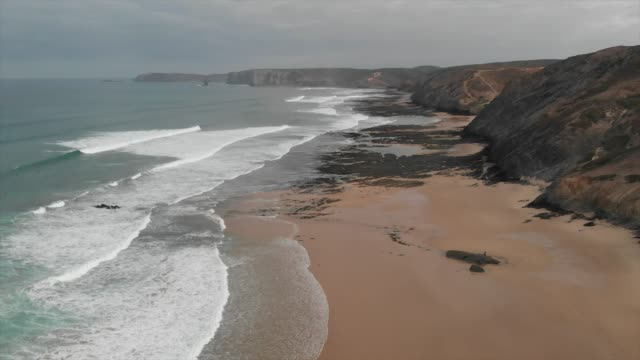 aerial drone view of the deserted empty rocky beach and cliffs in portugal. - slow motion - algarve stock-videos und b-roll-filmmaterial