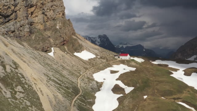 aerial drone view of the dolomites, flying over mountain hut on pass - hut stock videos & royalty-free footage