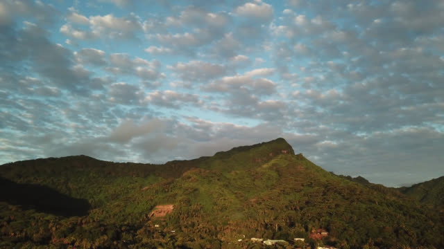 stockvideo's en b-roll-footage met aerial drone view of the mountain and the sea with a light of end of the day - huahine