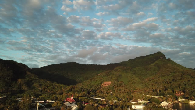 vidéos et rushes de aerial drone view of the mountain and village of fare with a light of end of the day - île d'huahine