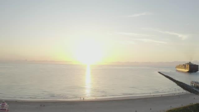 aerial drone view of the sea and a ship in south beach, miami, florida at sunrise - オーシャンドライブ点の映像素材/bロール