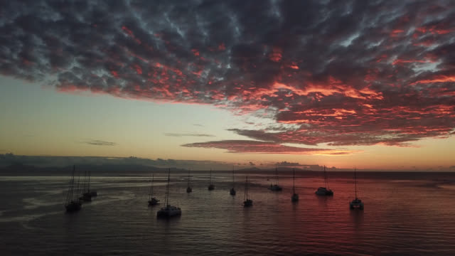 stockvideo's en b-roll-footage met aerial drone view of the sea and the sky after the sunset,with sailboats, red color cloud - huahine
