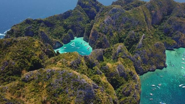 vídeos de stock e filmes b-roll de aerial drone view of tropical maya bay and limestone cliffs, phi phi islands, thailand - maia