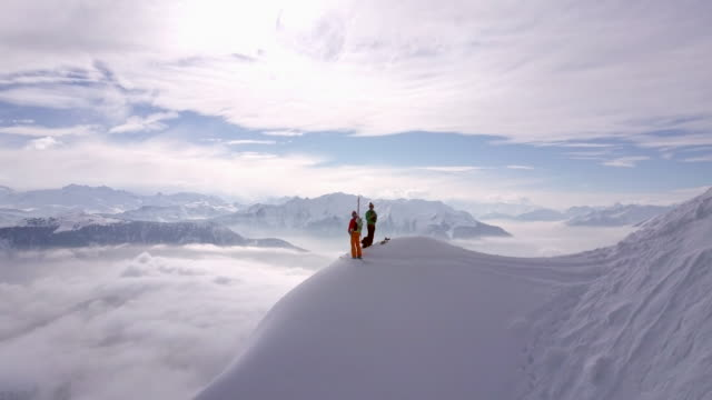 aerial drone view of two mountain climbers on top of a snow covered mountain. - mont blanc stock videos & royalty-free footage