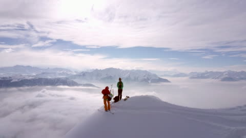 aerial drone view of two mountain climbers on top of a snow covered mountain. - extreme sports stock videos & royalty-free footage