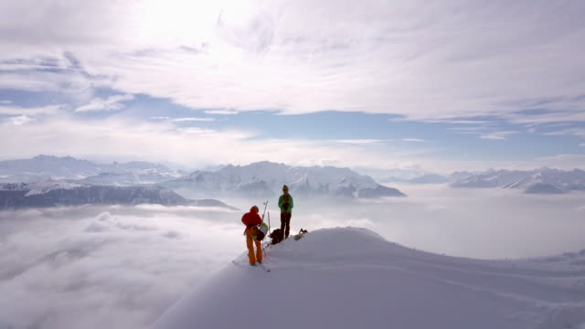 aerial drone view of two mountain climbers on top of a snow covered mountain. - passione video stock e b–roll