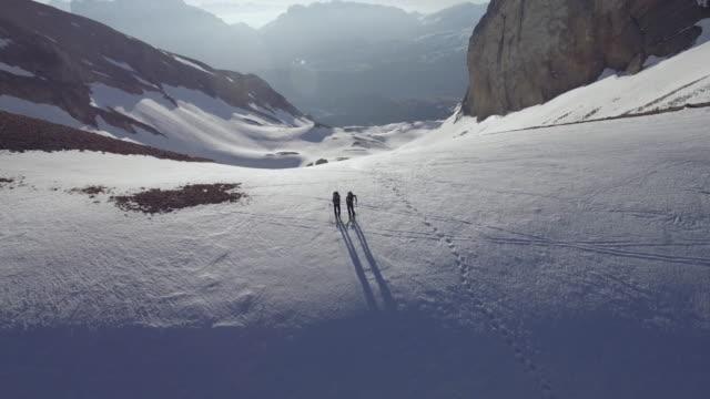 aerial drone view of two skiers skiers cross country skiing up a mountain. - längd bildbanksvideor och videomaterial från bakom kulisserna