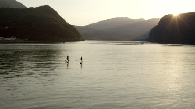 luft-drohnenansicht von zwei stand up paddle boardern (sup), die bei sonnenuntergang auf dem see paddeln - paddel stock-videos und b-roll-filmmaterial
