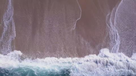 aerial drone view of waves breaking on the beach ocean coastline waves sea. - aerial view stock videos & royalty-free footage