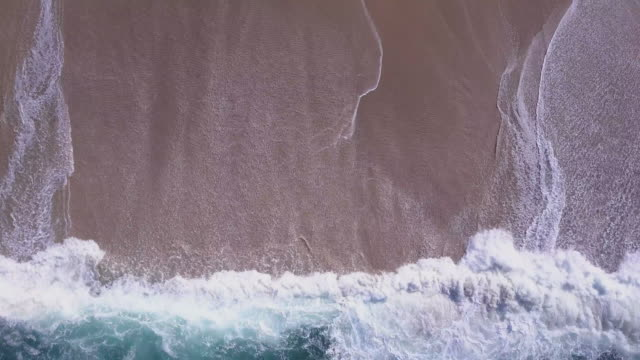 aerial drone view of waves breaking on the beach ocean coastline waves sea. - serenità video stock e b–roll
