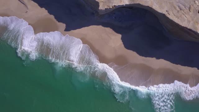 Aerial drone view of waves breaking on the beach ocean coastline waves sea.