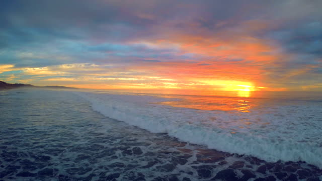 aerial drone view of waves rolling in during sunset - audio disponibile sulla versione digitale video stock e b–roll