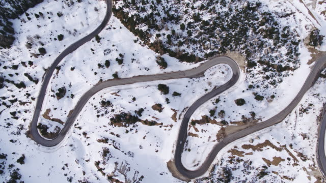 Aerial drone view of winding road in winter, Dolomites, Italy