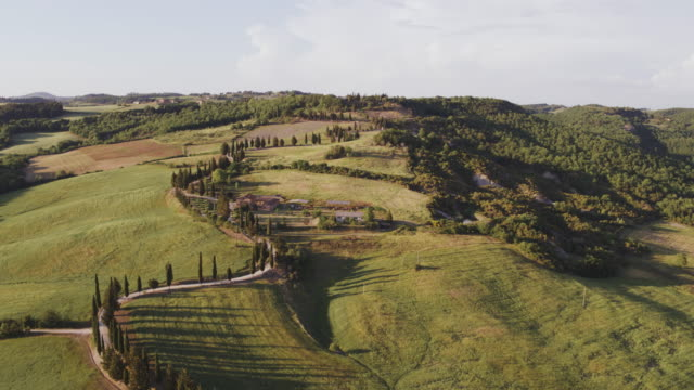 aerial drone view of winding road on a hill at sunset, tuscany, italy - toskana stock-videos und b-roll-filmmaterial