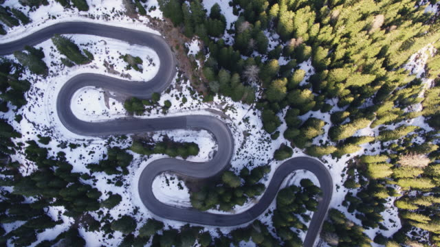 Aerial drone view of winding road through forest in winter