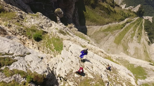 Aerial drone view of wingsuit pilot jumping off cliff