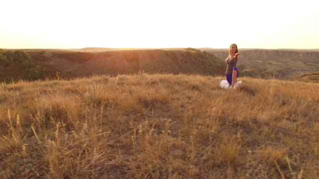 aerial drone view of woman doing yoga at viewpoint over canyon - pedal pushers stock videos & royalty-free footage