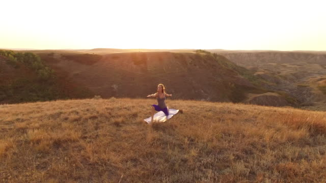 Aerial drone view of woman doing yoga at viewpoint over canyon