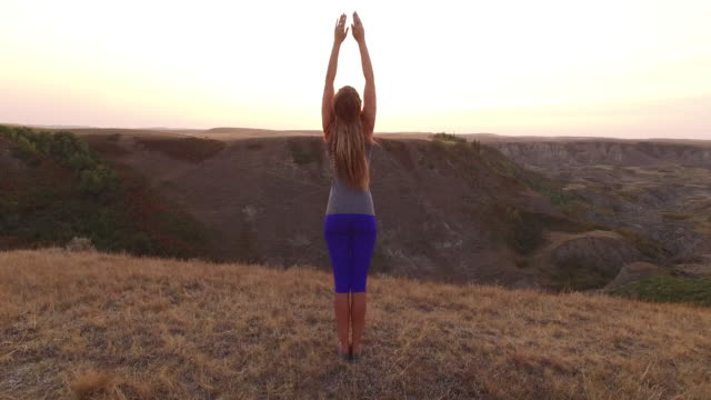 aerial drone view of woman doing yoga at viewpoint over canyon - body care stock videos and b-roll footage