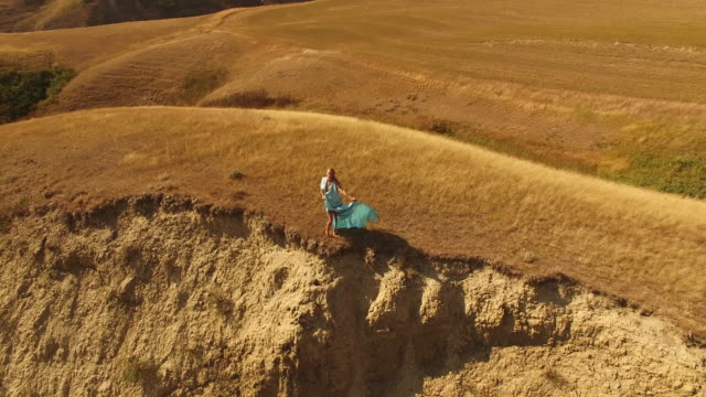 Aerial drone view of woman in dress looking out over canyon