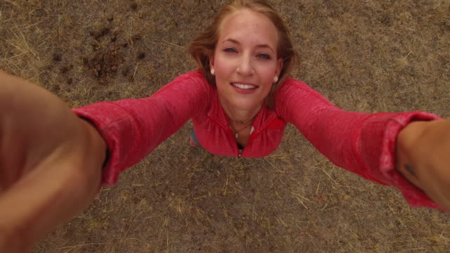 aerial drone view of woman looking up at camera - zoom out stock-videos und b-roll-filmmaterial