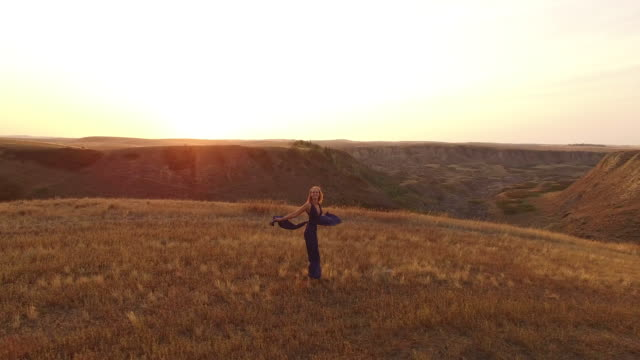 aerial drone view of woman skipping through field overlooking canyon - evening gown stock videos and b-roll footage