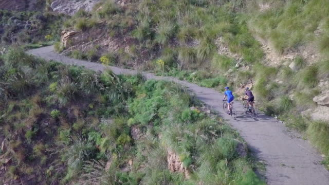 aerial drone view of women cycling on bicycles, riding on road bikes in italy. - time-lapse - aspirations stock videos & royalty-free footage