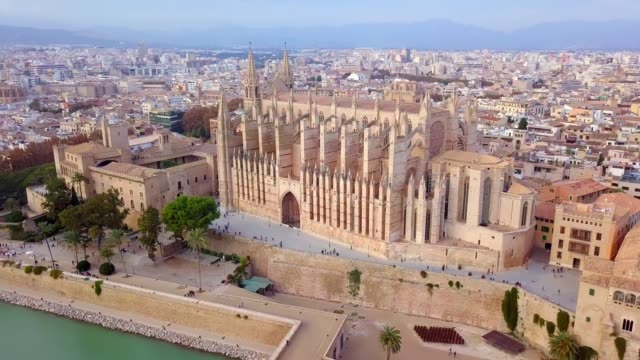 aerial drone view palma de mallorca cathedral was built on a cliff rising out of the sea. picturesque panorama majorca cityscape mountain range cloudy sky residential buildings from top. spain - chapel stock videos & royalty-free footage
