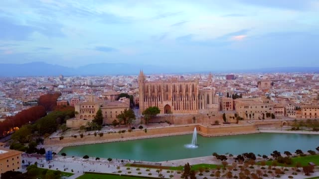 aerial drone view palma de mallorca cathedral was built on a cliff rising out of the sea. picturesque panorama majorca cityscape mountain range cloudy sky residential buildings from top. spain - palma stock videos & royalty-free footage