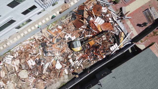 aerial drone view spinning directly above looking down on a home demolition and destroyed by excavator for new house construction. - building activity stock videos & royalty-free footage