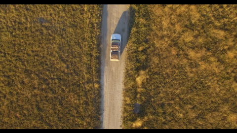 aerial drone view straight down, driving a pickup truck on a dirt road bush brush in africa during a safari. - time-lapse - truck stock videos & royalty-free footage