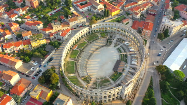 aerial drone view sunset scene of pula arena, a roman amphitheatre with adriatic sea in pula. istria, croatia - croazia video stock e b–roll