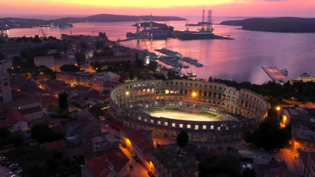 aerial drone view sunset scene of pula arena, a roman amphitheatre with adriatic sea in pula. istria, croatia - amphitheatre stock videos & royalty-free footage