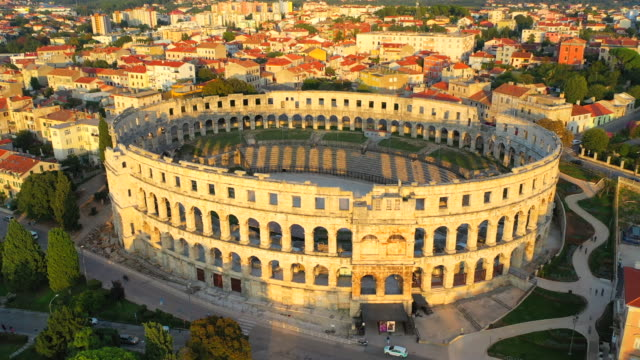 aerial drone view sunset scene of pula arena, a roman amphitheatre with adriatic sea in pula. istria, croatia - antiquities stock videos & royalty-free footage