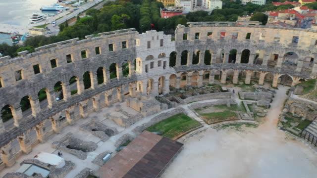 aerial drone view sunset scene of pula arena, a roman amphitheatre with adriatic sea in pula. istria, croatia - amphitheatre stock videos & royalty-free footage