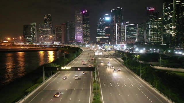 aerial drone view traffic on the highway road with construction of the city skyline at night in singapore - singapore stock videos & royalty-free footage