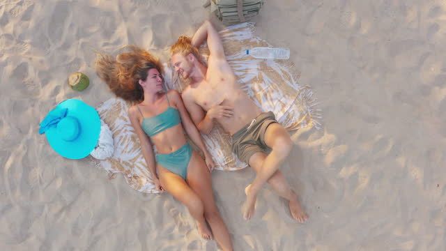 aerial drone view,happy honeymoon to couples of latin american and hispanic ethnicity relax lying down with boyfriend on the white sand of beach.drone point of view,moving activity,busy,progress,vitality,vacations concept - wonderlust stock videos & royalty-free footage