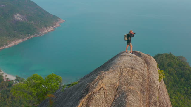 aerial drone view,happy of freedom travelers age 25 yearold of caucasian ethnicity makes beautiful pictures on camera enjoying travel holidays on top of mountain ocean summit.travel cinemagraphs concept. - wonderlust stock videos & royalty-free footage